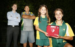L to R: Ben Cottee from Royal Lifesaving, Sylvania Heights FC President Trent Jordan with Players Amelia Porter -8 and Koby Porter -13 , holding the new defibrillator